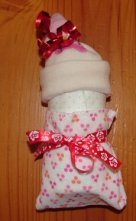 rolled diaper, fixed washcloth and baby sock as hat, sock fixed with a ribbon
