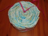 fully filled cake setting ring with diapers from above, ribbon hanging out