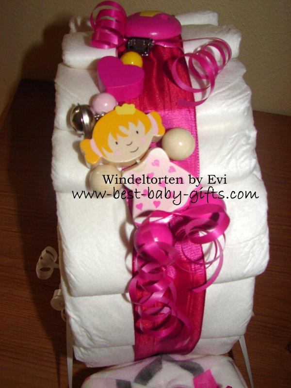 a pacifier chain clipped to the pink ribbon of the diaper snail