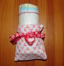 rolled diaper and how to fix the washcloth around it, fixed with ribbon