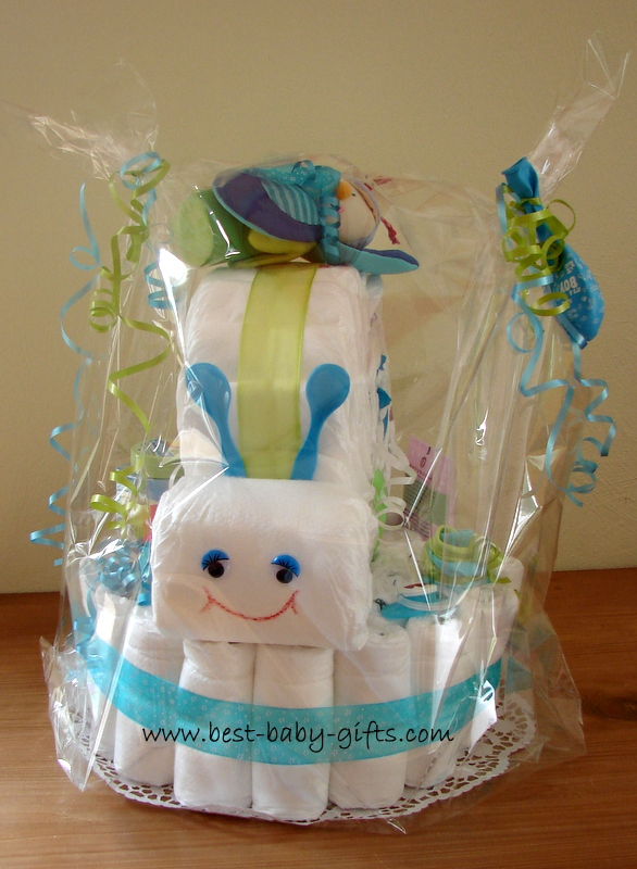 a diaper snail on a big round diaper cake base, the snail has blue baby spoon feelers and there's a blue and green baby toy on top, the snail is wrapped in clear foil gift wrap