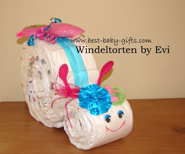 a girl diaper snail with pink and turquoise accessories, a lavish head band in turquoise and green decorates its head
