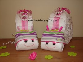 two homemade diaper snails side by side with colorful striped hats
