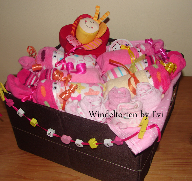 6 pink and yellow diaper babies, baby toys and baby utensils in a large brown box