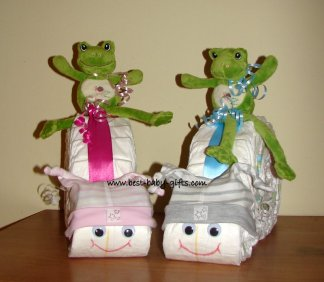 two diaper snails side by side, one for a girl in pink, the other for a boy in gray, little green plush frogs riding on both