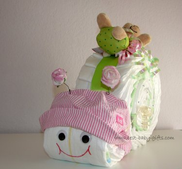 a diaper snail with a pink sun hat and a green cuddly toy on top, it has a big red smiling mouth and two roses as feelers