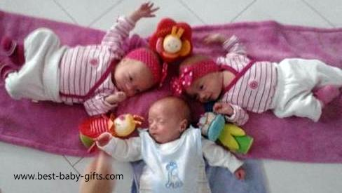 newborn triplets, laying on their back, enjoying each others company, 2 girls dressed in pink, one boy dressed inblue