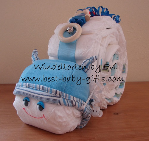 a diaper snail with blue ribbon, a blue hat and a blue toy on top, it has friendly blue wobbly eyes