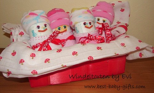4 happy diaper babies for girl in a little red basket