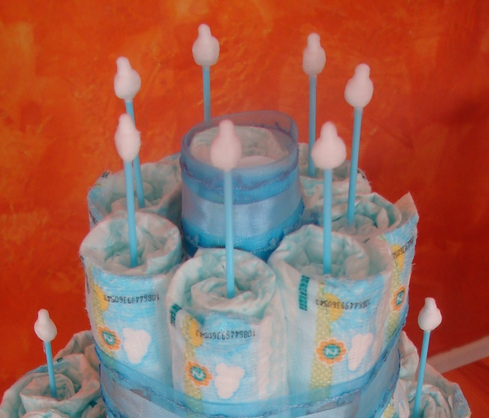 oberer Teil einer Windeltorte, mit blauem Schmuckband und Wattestäbchen als Kerzen