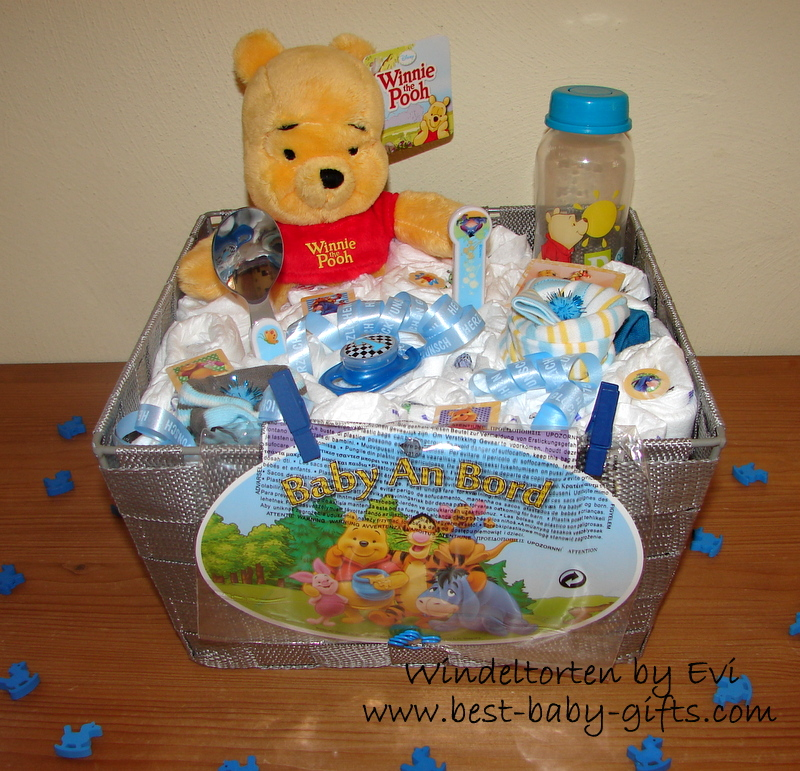 a grey basket filled with diapers and baby gear and a cuddly Winnie The Pooh, attached sign saying 'baby  on board'