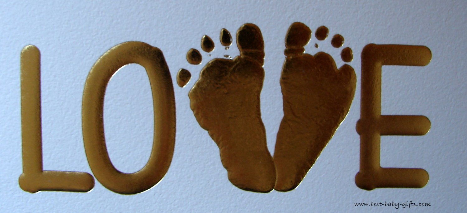 LOVE written in big, golden letters. The V is formed by two baby feet. White background.