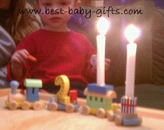 baby boy and a birthday train with two candles burning, also the No 2 is riding on the train