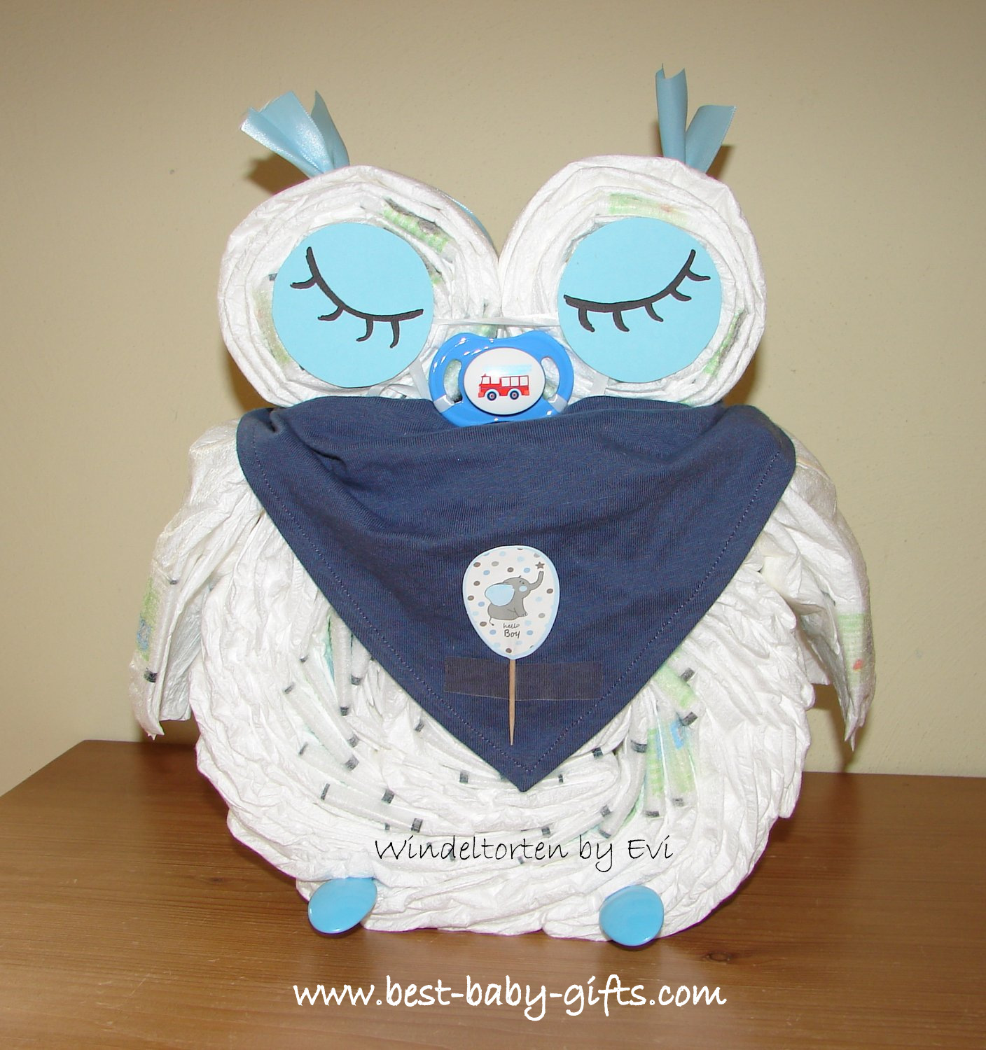 diaper owl for baby boy in blue with sleepy eyes, a blue bib and a pacifier with a red fire truck on
