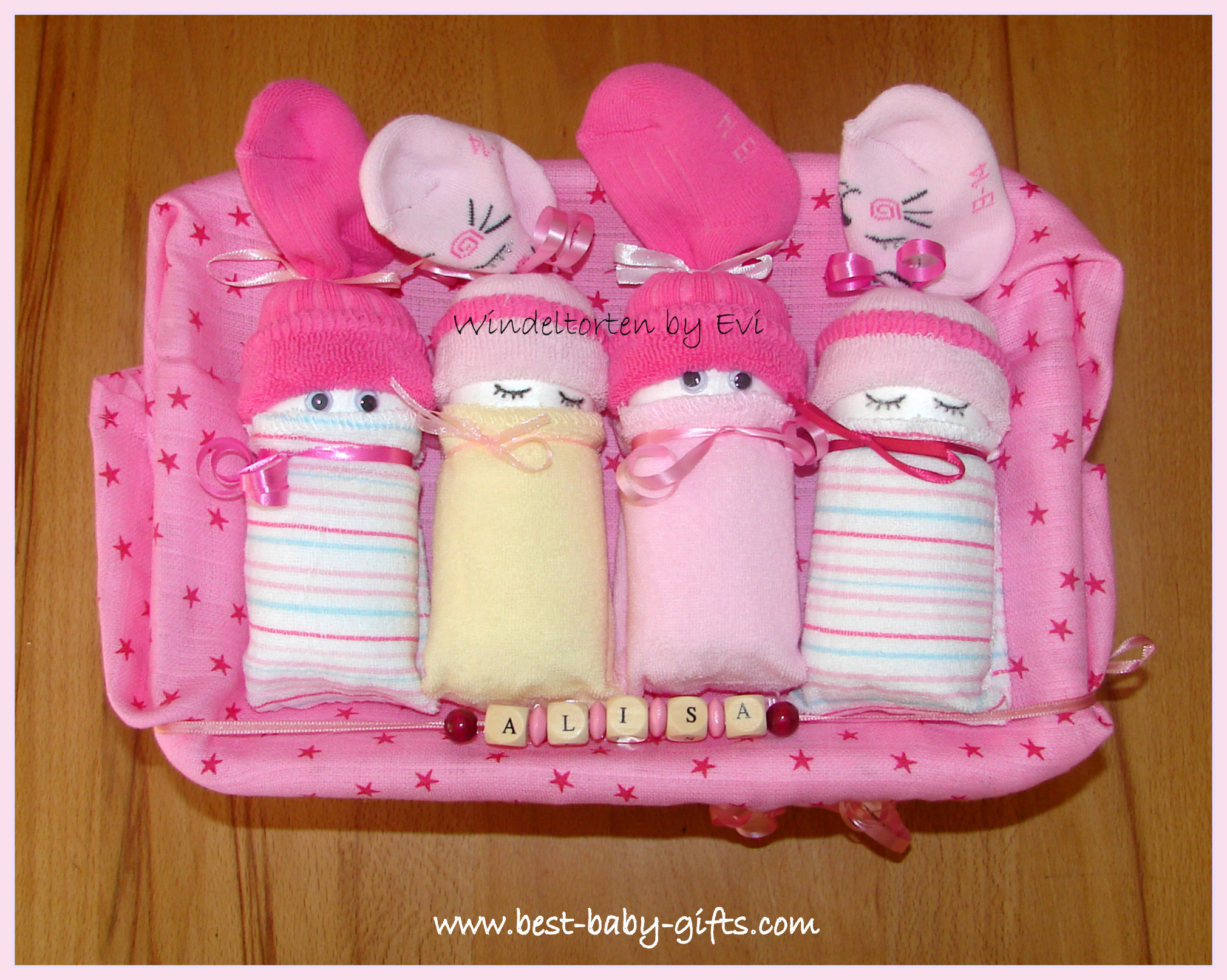 4 diaper babies in a box, in pink and yellow colors for a baby girl, personalized with a name band and wooden letters 'Alisa'