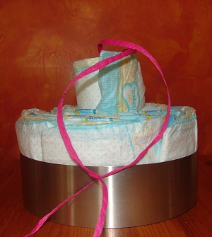 cake setting ring with diapers and last diaper with ribbon inside inserted on top but still sticking out