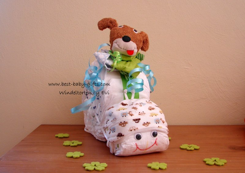 a white, brown and green diaper snail with a cuddly dog toy on top