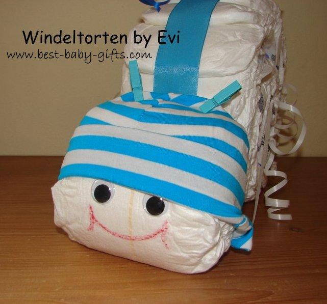 head of a diaper snail with a blue and white striped baby hat and two little blue clothes pegs as feelers