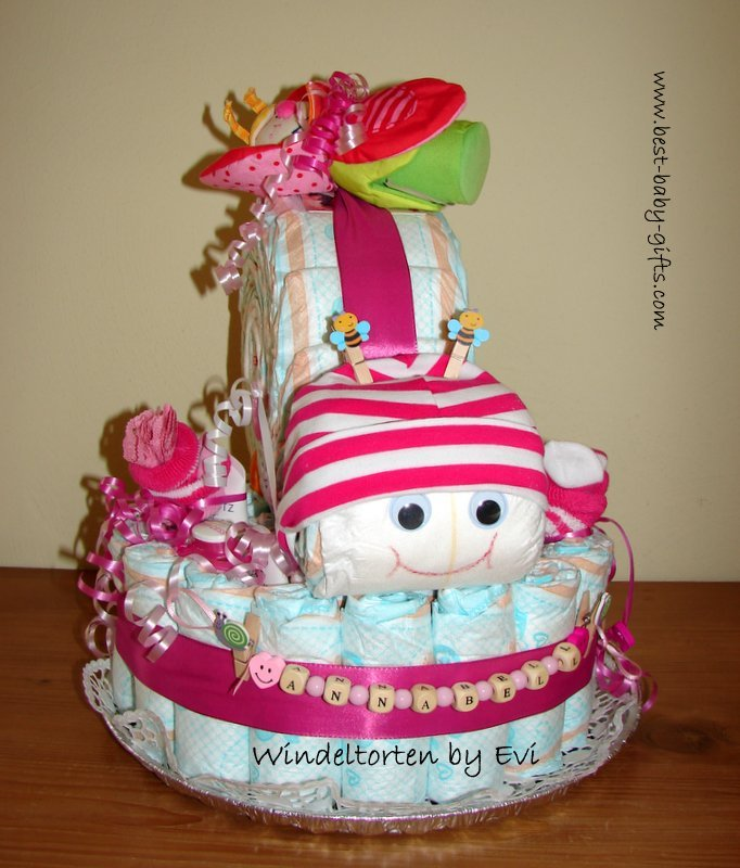 a diaper snail on a big round diaper cake base, the snail wears a striped baby hat in pink and white, there's a pink and green baby toy on top