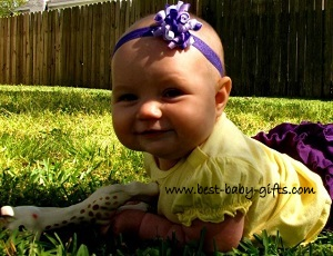 baby girl crawling on grass with Sophie the giraffe toy