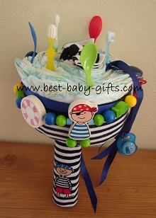boy diaper bouquet in blue with wooden pirate figurine, feeding spoons and baby toothbrush sticking out