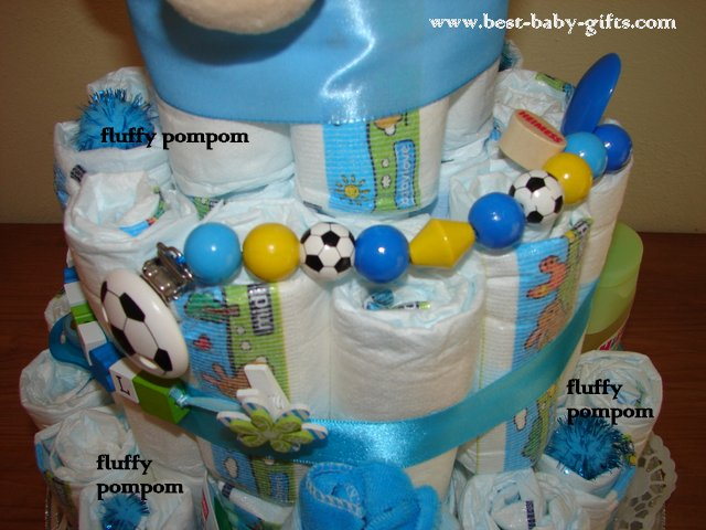 details of the diaper cake on the left side, pacifier chain with soccer balls attached to the cake