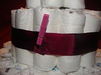 Windeln mit dunkelrotem Schmuckband und Klammer um das Band zu halten