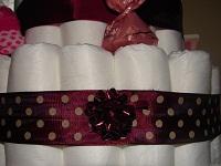 Windeln mit dunkelrotem Schmuckband mit weißen Punkten und aufgeklebter Fertigschleife um die 'Schnittstelle' zu verdecken