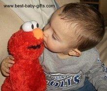 baby boy kissing a cuddly Elmo puppet