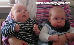 twins: baby boy and baby girl sitting on someone's lap