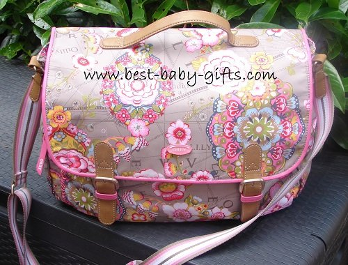 a light-brown messenger diaper bag with a big, prominent pink and yellow boho / flower design