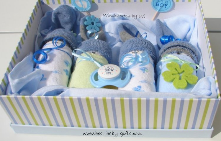 4 diaper babies and decorations, in a cardboard box with blue and green stripes