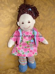 soft doll with brown hair in a pony tail, a pink dress with flowers and blue shoes