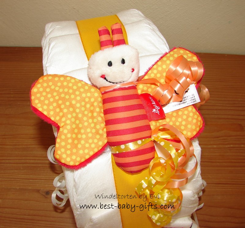 a red and yellow butterfly toy fixed with a ribbon on the snail's top